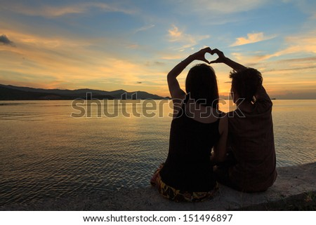 couple makes heart symbol at dusk - stock photo