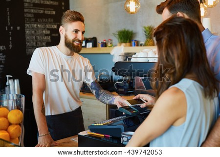 Couple making payment with smartphone at coffe shop - stock photo