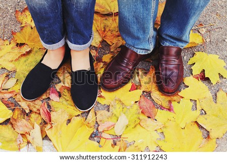 Couple Man and Woman Feet in Love Romantic Outdoor with Autumn season nature on background Fashion trendy style. Top view on shoes. Photo toned style instagram filters - stock photo