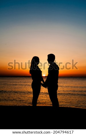 Couple Man and Woman holding hands in Love staying on Beach seaside with Sunrise scenery. People, Romantic, relationship and Friendship concept. - stock photo