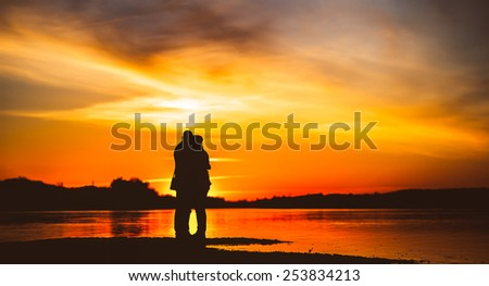 Couple Man and Woman Hugging in Love staying on Beach seaside with Sunset - stock photo