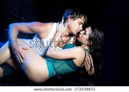 Couple man and woman in aqua studio shower, hug, love, sexy. Beautiful lady with long curly hair, bright red lips, passion. Free place on photo for new advertising refreshing deodorant or shampoo. - stock photo