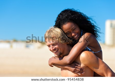 couple - man and woman - on the beach having lots of fun, the man is carrying the woman pack back - stock photo
