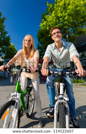 Couple - man and woman - riding their bikes or bicycles in their free time and having fun on a sunny summer day - stock photo