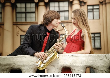 Couple. Man with sax and woman in the park - stock photo