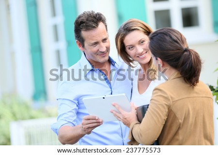 Couple meeting real-estate agent outside new property - stock photo