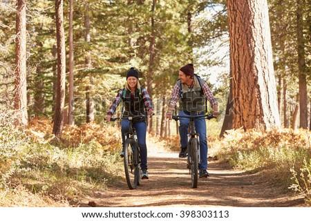 Couple mountain biking through forest, California - stock photo