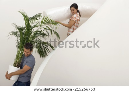 Couple moving house, man carrying large pot plant down staircase, woman carrying dust sheet, smiling - stock photo