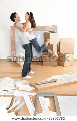 Couple moving in happy and excited in new home. Young interracial couple with moving boxes and furniture assembly in new house or apartment. Caucasian man and Asian woman embracing. - stock photo