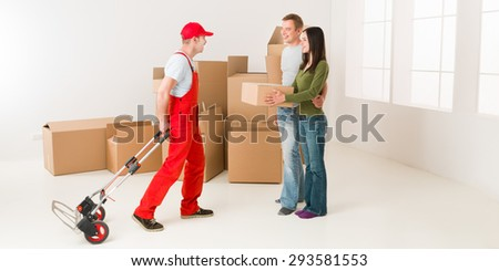 couple moving in new home and receiving package from delivery man - stock photo
