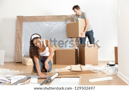 Couple moving in new home house. Young interracial couple in moving in mess. Asian woman, Caucasian man. - stock photo