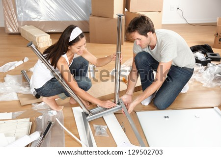 Couple moving in together assembling furniture table. Young interracial couple in new house or apartment home working together to assemble table. Asian woman, Caucasian man. - stock photo