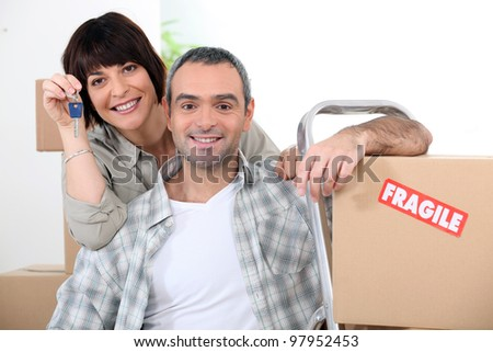Couple moving into new home with doorkeys and boxes marked fragile - stock photo