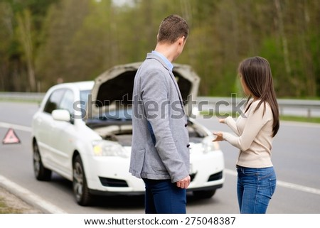 Couple near broken car on a highway roadside  - stock photo