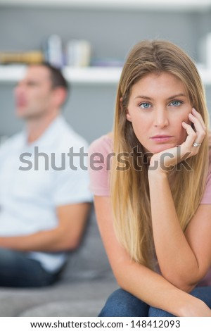 Couple not talking after a dispute on the couch with woman looking at camera in living room at home - stock photo