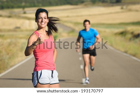 Couple of athletes on running workout in country road . Sporty woman and man exercising together on summer. Healthy and sport lifestyle concept. - stock photo