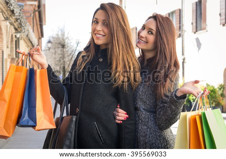 Couple of attractive caucasian girls doing shopping togheter - they are holding their bags smiling at the camera - shopping, people and lifestyle concept - stock photo