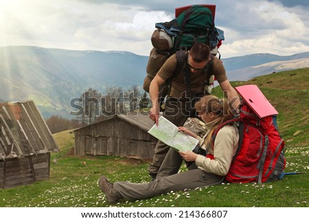 Couple of backpackers on top of mountain with map. - stock photo