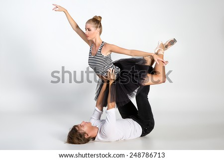 Couple of ballet dancers posing over white background - stock photo