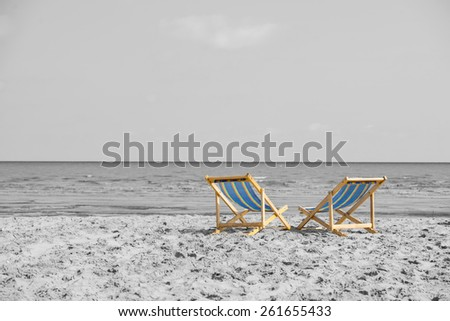 Couple of beach chairs look outward to the sea over black and white background - stock photo