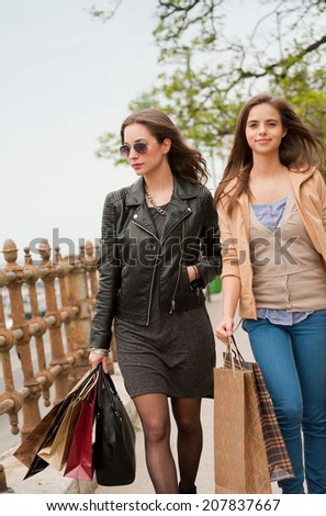 Couple of beautiful young brunette women with shopping bags outdoors. - stock photo