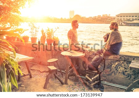 Couple of best friends travelers talking at sunset - Travel concept around the world with exclusive destinations - Young hipster wanderers relaxing and enjoying alternative holidays life experiences - stock photo