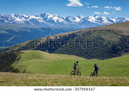 Couple of bicyclists traveling among green hills and looking at snowy mountains  - stock photo