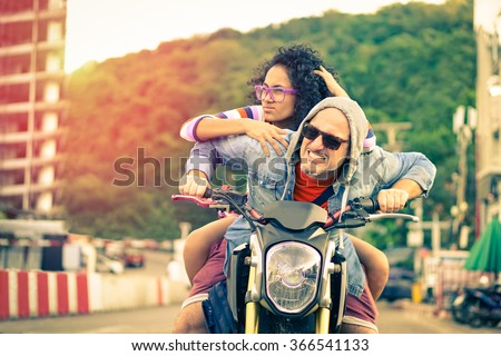 Couple of bikers riding motorbike having fun driving as crazy on urban road at sunset -  Cool man and beautiful girl on sport motorcycle with funny facial expression - Concept of risk focus on male - stock photo