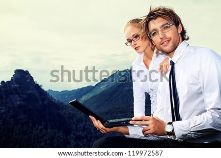 Couple of business people  standing on the top of a mountain with a laptop. - stock photo