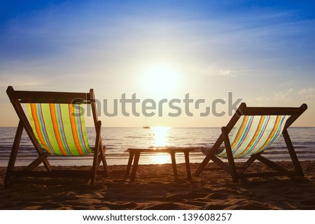 couple of chairs and table on the beach at sunset - stock photo
