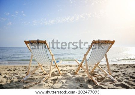 couple of chairs on sandy beach at sunset looking for the blue sea - relaxation concept - stock photo