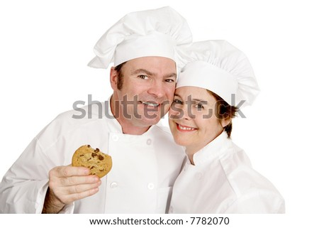 Couple of chefs smiling and enjoying a cookie.  Isolated on white. - stock photo