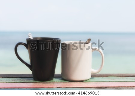Couple of coffee cups in the morning on retro terrace facing seascape   - stock photo