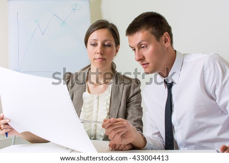 Couple of colleagues working on a project at the office - stock photo