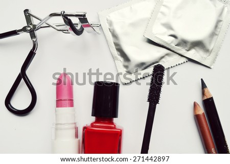 Couple of condoms and a cosmetics set with black mascara, pink and red nail polish and lipstick and eyelash curler isolated on white - stock photo