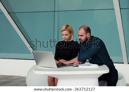 Couple of confident leaders searching together in Internet via laptop computer place for the opening new office, smart man and woman reading information on net-book about the results of their work - stock photo