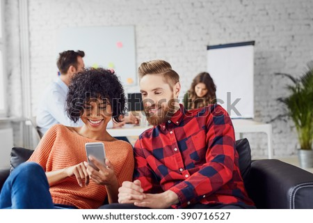 Couple of coworkers, students sharing together smartphone, sitting at creative office on couch - stock photo