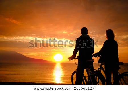 Couple of cyclists at the beach at sunset. - stock photo