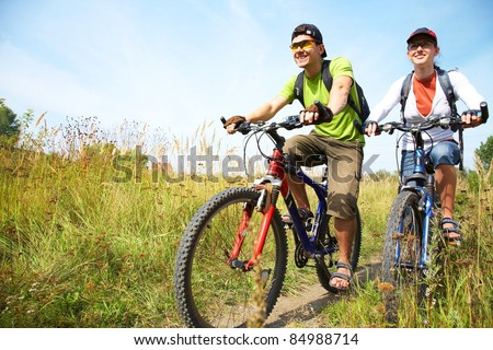Couple of cyclists riding bicycles in countryside - stock photo