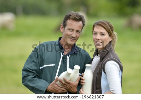 Couple of farmers in field holding milk bottles - stock photo