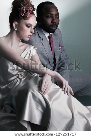 Couple of fashion models sitting - stylish black american man and redhead fashionable woman - stock photo