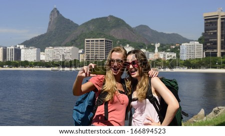 Couple of female backpackers making a self portrait in Rio de Janeiro with Christ the Redeemer in background. - stock photo