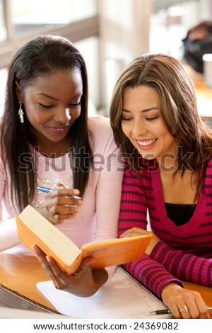 Couple of female students with a book in a classroom - stock photo