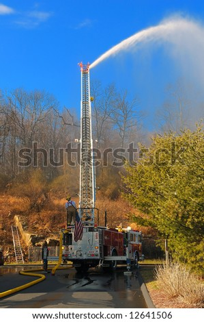 Couple of fire fighters spraying water to stop the forest fire - stock photo