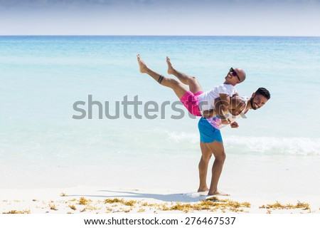 Couple of friends having fun at the beach in the Caribbean - stock photo