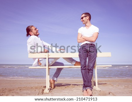 couple of friends sitting on a bench and having fun - stock photo