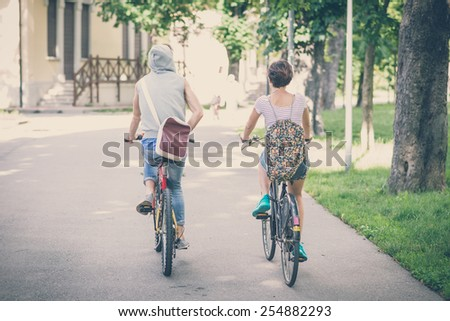 couple of friends young  man and woman riding bike in the city - stock photo