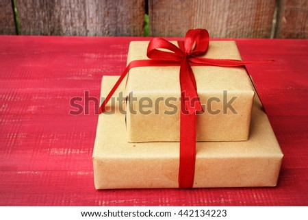 Couple of gift boxes wrapped with simple brown craft paper and decorated with satin ribbon wine red color with a bow. Simple composition in a bright color Rustic decor elements - stock photo