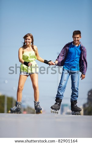 Couple of happy teens rolling on skates on the road - stock photo