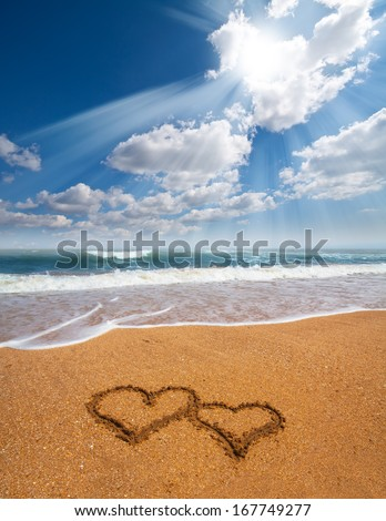 couple of hearts drawn on the sand of a beach - stock photo